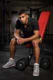 Young man sitting on bench at gym Stock Photography
