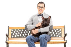 Young man sitting on bench with his dog Royalty Free Stock Photography