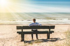 Young man sitting on a bench near sea Stock Image
