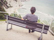Young man sitting on bench overlooking sea Stock Images