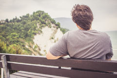 Young man sitting on bench overlooking sea Stock Photo