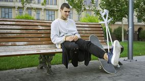 Young man sitting on the bench in the park while listening to music on his cellphone then taking crutches and skateboard. Attractive young man sitting on the stock footage