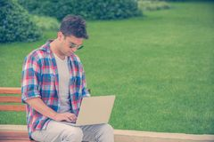 Young man sitting on bench in the park and working on laptop out. Handsome fashionable guy sitting on bench in the park with his hands on computer keyboard and Royalty Free Stock Images