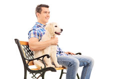 Young man sitting on a bench with a puppy Stock Photos