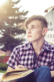 Young man sitting on bench and readindg book Royalty Free Stock Photo