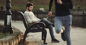 Young man sitting on the bench and reading book in park stock footage