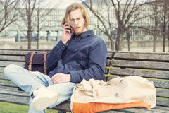 Young man sitting on bench and talking on the phone Stock Photography