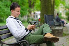 Young man sitting on the bench and using tablet device on beauti Stock Photography