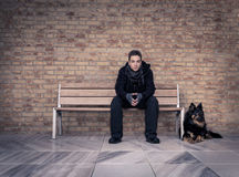 Young man sitting on a bench with your best four-legged friend Royalty Free Stock Photo