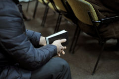 Bible in Man's Hands. Young man sitting with bible in his hands Stock Photos