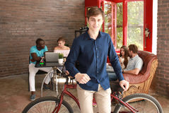 Young man sitting on a bicycle in a modern office. Royalty Free Stock Photos