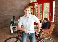 Young man sitting on a bicycle in a modern office. Royalty Free Stock Images