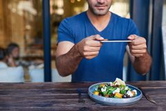 Young man photographing his salad at a bistro table stock images