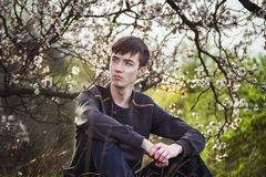 Young man sitting by blooming tree Royalty Free Stock Photos