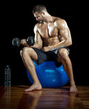 Young man sitting on blue gym ball. Royalty Free Stock Images