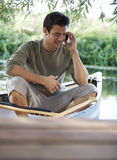 Young man sitting in a boat talking on a mobile phone Stock Images