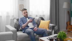 Young man sitting bored on the sofa, watching TV and changing channels stock video