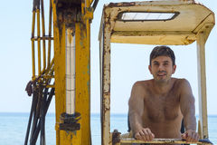 Young man sitting in a bulldozer at the beach Royalty Free Stock Photography