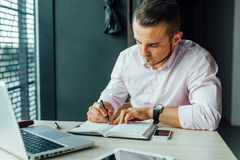 Young man sitting in cafe and adding new meeting in his calendar Royalty Free Stock Photos