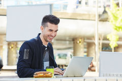 Young man sitting at cafe with coffee and sandwich working. Close up portrait of young man sitting at cafe outside with coffee and sandwich working Royalty Free Stock Images