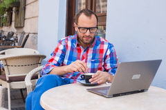 Young man sitting in cafe with laptop and coffee. Stock Image