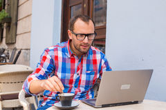 Young man sitting in cafe with laptop and coffee. Royalty Free Stock Image