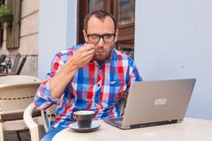 Young man sitting in cafe with laptop and coffee. Stock Photo