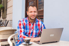 Young man sitting in cafe with laptop and coffee. Royalty Free Stock Photography