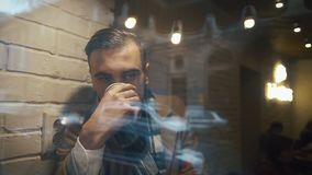 Young Man Sitting In The Cafe near the window and Drinking Cofee from a Paper Cup.The guy is dressed in cloak stock footage
