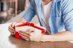 Young man sitting in cafe restaurant and holding a present gift giving to someone special for special occasion. Young man sitting in cafe restaurant and holding Stock Photography
