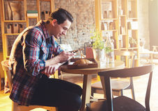 Young man sitting at a cafe, using a cell phone Royalty Free Stock Photo