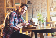 Young man sitting at a cafe, using a cell phone Stock Photo