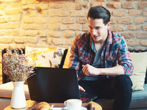 Young man sitting at a cafe, using a laptop Royalty Free Stock Images