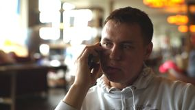 Young man sitting in cafe using phone. Young man talking on the phone in the restaurant stock footage