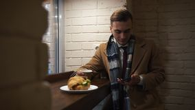 Young Man Sitting In The Cafe, using smartphone and Drinking Cofee from a Paper Cup.The guy is dressed in cloak stock footage