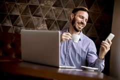 Young man sitting in cafes, drinking coffee and looking with a sm Stock Image