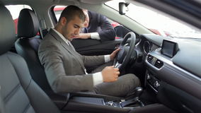 Young man sitting in car. Auto business, car sale, technology and people concept - happy male with car dealer in auto show or salon. Young man with a salesman stock video footage