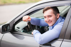 Young man sitting in car holding car keys Royalty Free Stock Image