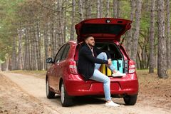 Young man sitting in car trunk loaded with suitcases stock image