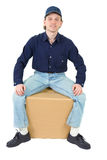 Young man sitting on the cardboard box Royalty Free Stock Images