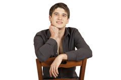 Young man sitting on a chair Royalty Free Stock Images