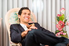 Young man sitting on chair in hotel room Royalty Free Stock Photo