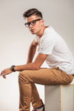 Young man sitting on a chair looking smart royalty free stock photography