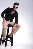 Young man sitting on chair looks at camera Royalty Free Stock Photography