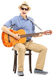 Young man sitting on a chair and playing acoustic guitar Royalty Free Stock Photography