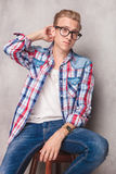 Young man sitting on a chair while scratching his head. Royalty Free Stock Photography