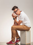 Young man sitting on a chair thinking. And looking at the camera Royalty Free Stock Images