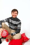Young man sitting with Christmas pillows  on white backg Royalty Free Stock Photo