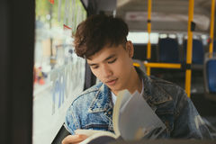 Young man sitting in city bus and reading a book. Stock Photos