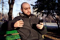 Young man sitting in city park with smart phone and drinking Royalty Free Stock Photos